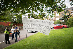 """© Licensed to London News Pictures. 04/08/2019. Whaley Bridge, UK. Poster reading """" Keep your chinook up """" as residents (pictured in the background) bring food and drinks for emergency service workers . Residents just outside the cordon erect signs thanking emergency services . Further homes have been evacuated overnight and more rain is forecast today (Sunday 4th August) in the town of Whaley Bridge in Derbyshire after earlier heavy rain caused damage to the Toddbrook Reservoir , threatening homes and businesses with flooding. Photo credit: Joel Goodman/LNP"""