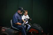 Mariners head groundskeeper Bob Christofferson gives a lawn mower ride to outfielder Seth Smith's son Cruise, 4, at Safeco Field as he preps Safeco Field for a game against the Toronto Blue Jays, Sept. 20, 2016.