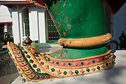 """09 MARCH 2009 -- BANGKOK, THAILAND:  The feet of a Garuda (Guardian) at Wat Arun. Wat Arun is a Buddhist temple (wat) in the Bangkok Yai district of Bangkok, Thailand, on the west bank of the Chao Phraya River. The full name of the temple is Wat Arunratchawararam Ratchaworamahavihara. The outstanding feature of Wat Arun is its central prang (Khmer-style tower). It may be named """"Temple of the Dawn"""" because the first light of morning reflects off the surface of the temple with a pearly iridescence. Steep steps lead to the two terraces. The height is reported by different sources as between 66,80 m and 86 m. The corners are surrounded by 4 smaller satellite prangs. The prangs are decorated by seashells and bits of porcelain which had previously been used as ballast by boats coming to Bangkok from China. The central prang is topped with a seven-pronged trident, referred to by many sources as the """"trident of Shiva"""". Around the base of the prangs are various figures of ancient Chinese soldiers and animals. Over the second terrace are four statues of the Hindu god Indra riding on Erawan. The temple was built in the days of Thailand's ancient capital of Ayutthaya and originally known as Wat Makok (The Olive Temple). In the ensuing era when Thonburi was capital, King Taksin changed the name to Wat Chaeng. The later King Rama II. changed the name to Wat Arunratchatharam. He restored the temple and enlarged the central prang. The work was finished by King Rama III. King Rama IV gave the temple the present name Wat Arunratchawararam. As a sign of changing times, Wat Arun officially ordained its first westerner, an American, in 2005. The central prang symbolizes Mount Meru of the Indian cosmology. The satellite prangs are devoted to the wind god Phra Phai..Photo by Jack Kurtz"""