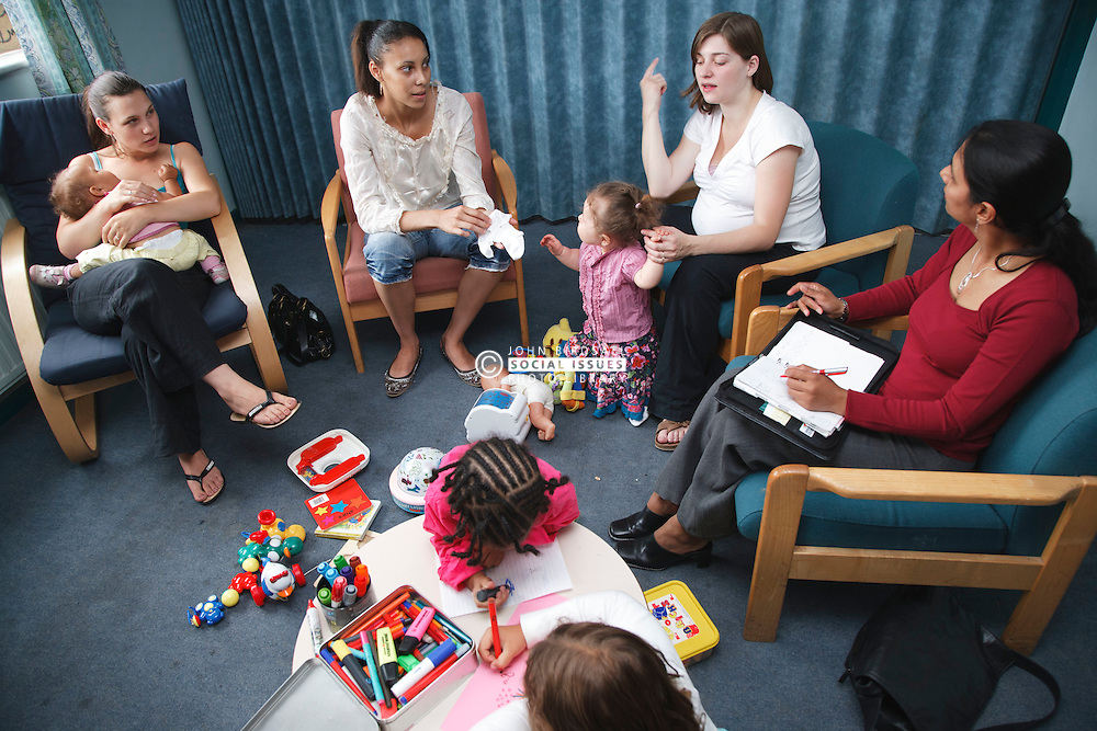 Social worker in discussion group with young mothers and children.