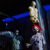 Emilia Tsosie sports a clown mask as she lingers in the slaughterhouse section of the Tsosie family haunted house in Deer Springs Wednesday.