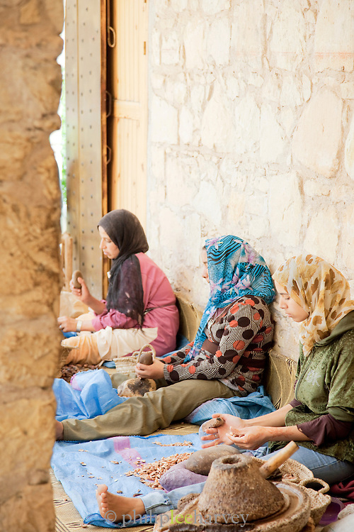 Women crack and crush palm nuts at a women cooperative near Essaouira in Morocco