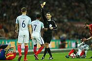 Referee Ovidiu Alin Hategan gives a yellow card to Raheem Sterling of England. England v Spain, Football international friendly at Wembley Stadium in London on Tuesday 15th November 2016.<br /> pic by John Patrick Fletcher, Andrew Orchard sports photography.