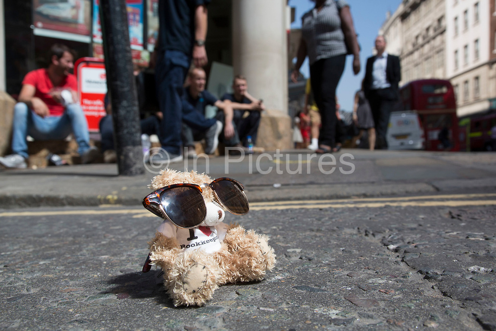 """London, UK. Thursday 5th September 2013. Boris the Bookmaking Bear wearing sunglasses. Urgent action in planned to """"cover up"""" the Walkie Talkie skyscraper in the City after sunlight reflected from the building melted a car on the streets below. Temperatures have been measured in excess of 50 degrees C, and as much as 70 degrees at it's peak. The 525ft building has been renamed the """"Walkie Scorchie"""" after its distinctive concave surfaces reflected a dazzling beam of light which has caused extensive damage to nearby buildings."""