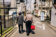 every day Street scene in Japan. Mature couple walking hand in hand