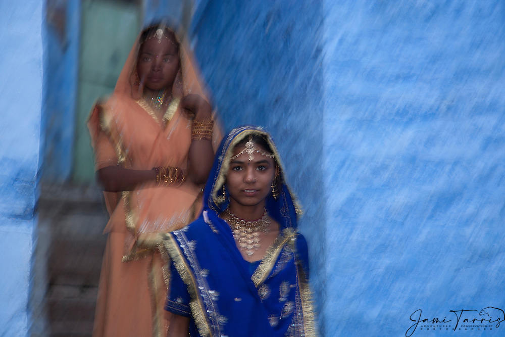 Motion blur of two girls in saris walking down the stairs in the blue city of Jodphur, Jodphur, Rajasthan, India