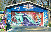 Colorful murals on the garage door, dirveway, and fence in an alley off Melrose Ave. in Los Angeles, California depict an abstract sea creature and a true representation of a sea turtle
