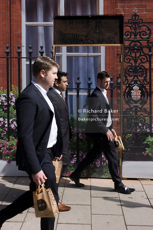 Businessmen bring back takeaway lunches, walking past the construction hoarding belonging to Claridges in Mayfair, Westminster.