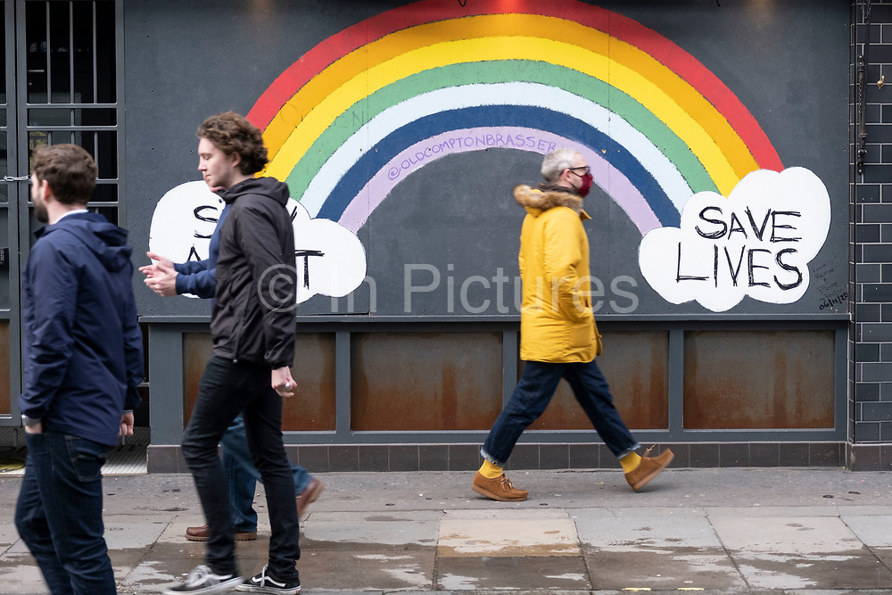People wearing face masks pass a stay alert, save lives NHS rainbow and clouds in Soho as the national coronavirus lockdown three continues on 29th January 2021 in London, United Kingdom. Following the surge in cases over the Winter including a new UK variant of Covid-19, this nationwide lockdown advises all citizens to follow the message to stay at home, protect the NHS and save lives.