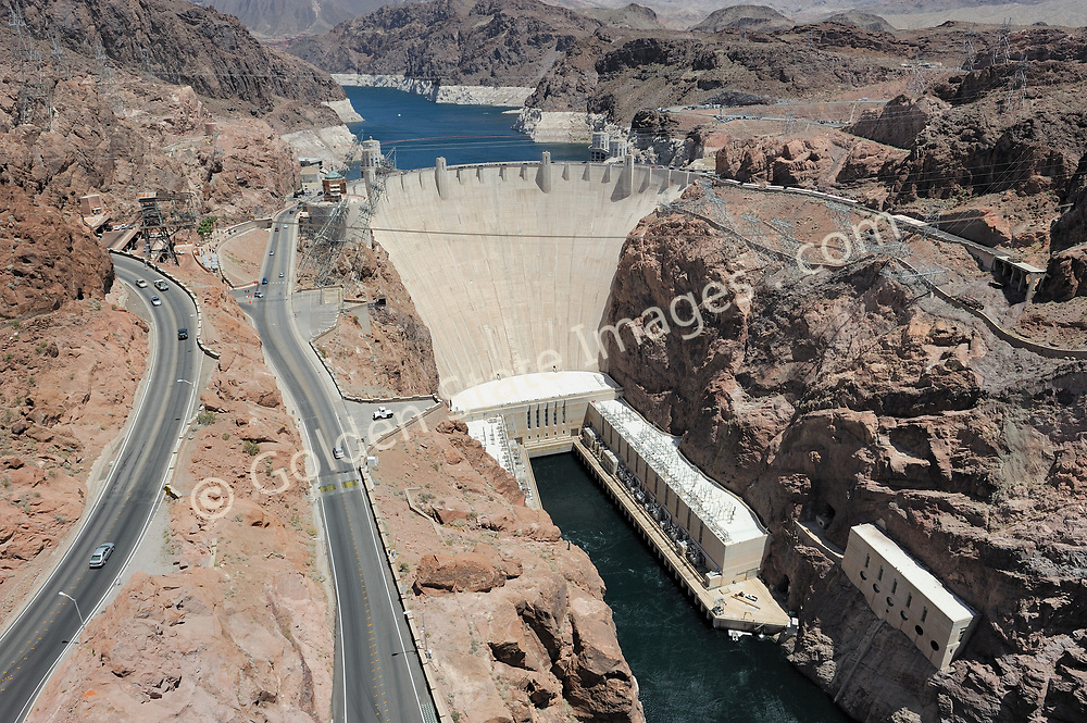 Hoover Dam is designed to never have the water level of Lake Mead overtop the dam. There are spillways on each side which route excess storage around the dam.