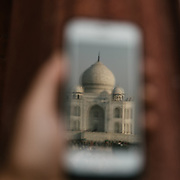 """Reflection of the Taj Mahal on a phone. Evening sunset walk at the <br /> Taj Mahal, meaning """"Crown of the Palaces"""", an ivory-white marble mausoleum on the south bank of the Yamuna river in the city of Agra."""
