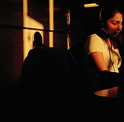 Virushka Sewprsad age 22, call centre agent works as the sun sets, the light catching her and forming a strong shadow of her head and headset against the wall. From the series Desk Job, a project which explores globalisation through office life around the World.