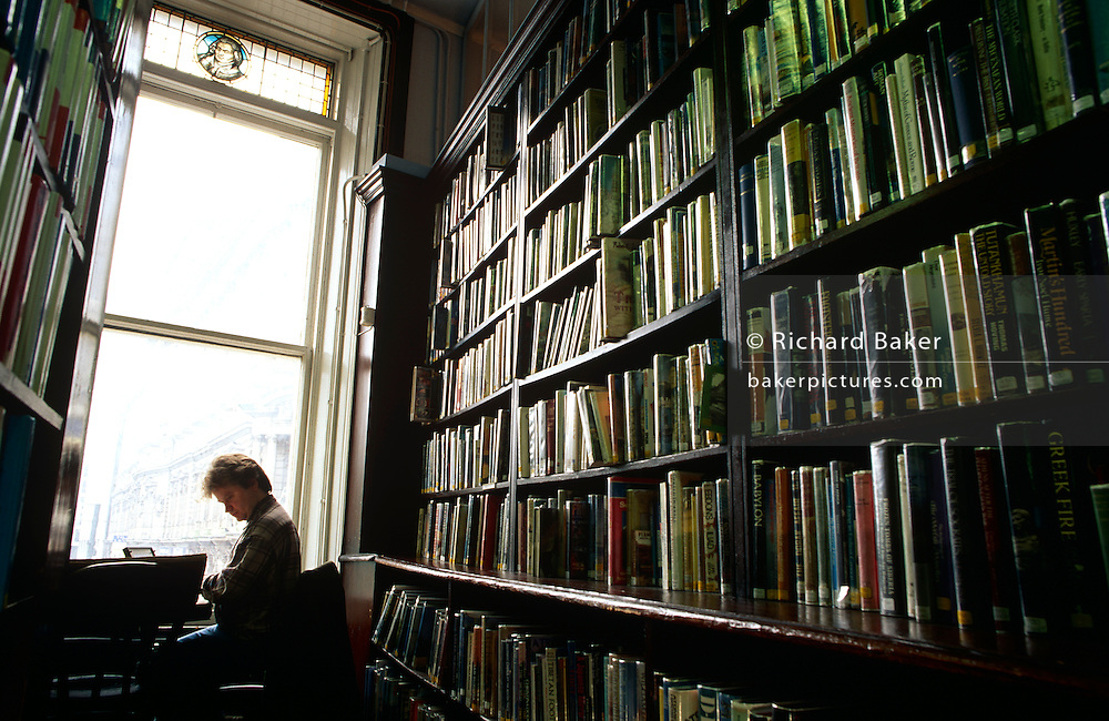 A reader looks through books in the Linen Hall Library in Belfast City Centre, Northern Ireland.