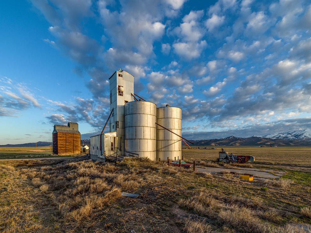 Grain Storage Elevators on the Camas Prairie at Corral Idaho catch the early morning sunshine in springtime.  Morning light illuminates a complex of Agriculture Elevators on the Camas Prairie in Southwest Idaho near Fairfield with breaking clouds in the blue sky above. Licensing and Open Edition Prints.