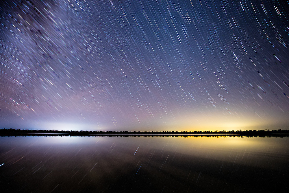 A long exposure at night captures the movement of stars and glow of the nearby townships in the still waters of Lake Broadwater. Lake Broadwater Conservation Park.