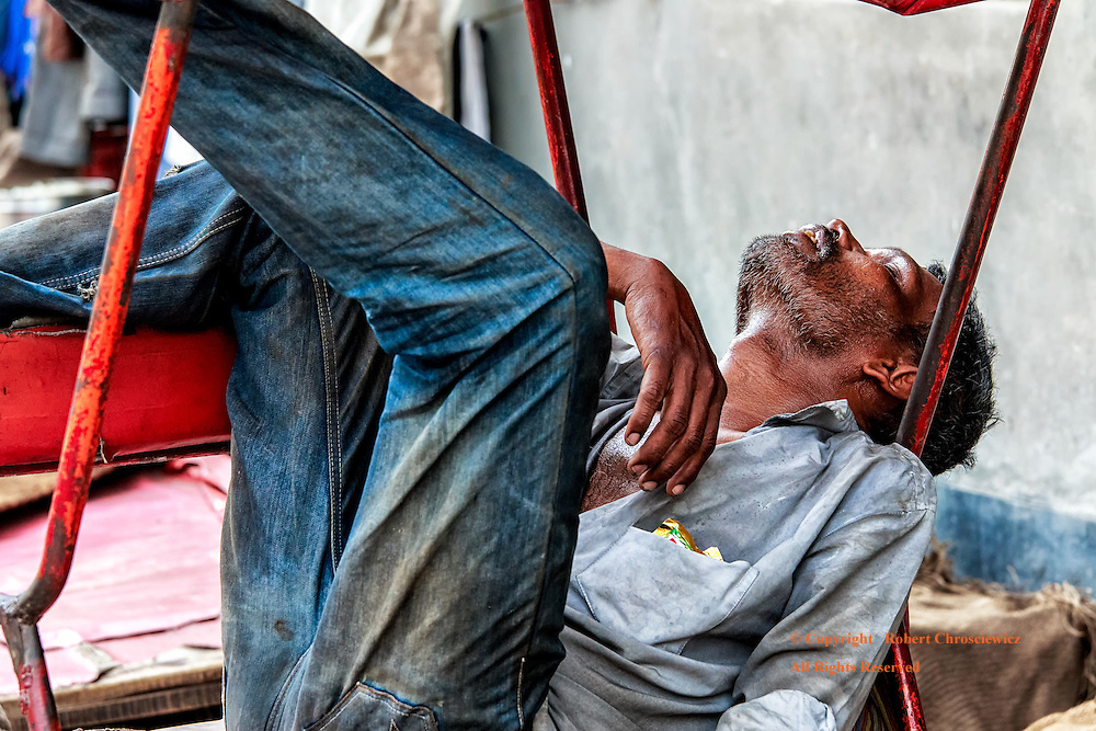 Rickshaw Exhaustion:  An exhausted rickshaw driver takes a well deserved nap, away from the intense mid day sun, in a back alley in New Delhi India.
