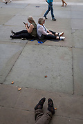 Tired visitors to London rest against each other on the pavement in Trafalgar Square, on 15th August 2017, in London, England.