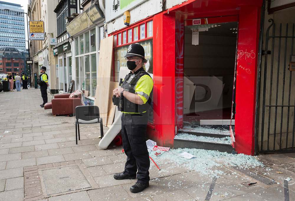 """© Licensed to London News Pictures; 04/06/2021; Bristol, UK. Bailiffs accompanied by around 100 police repossessed several buildings on High Street in the city centre which had been squatted, some since March. Officers had to remove barricade material from inside the building that the squatters had used to block entry, but those occupying the buildings had already left. Number 39 on High Street was the first building taken over, in March 2021 followed by numbers 45 and 46 which were been occupied. Yesterday a month-long closure order was put in place after police said there has been criminality and antisocial behaviour and owners had complained of damage to property. Police say there is a lot of litter and graffiti inside the buildings and there are reports of some extensive damage with a wall knocked down inside. Squatters had hung banners on the buildings including one saying """"Criminalising shelter is state violence"""" and campaigned against the Police Crime Sentencing and Courts Bill as part of the Kill the Bill campaign against criminalising squatting. Graffit saying """"Cops protest my rapist and kick me out of my home"""" could be seen on the wall of one of the premises that had been squatted. Photo credit: Simon Chapman/LNP."""