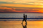 Couple Walking on the Beach at Sunset