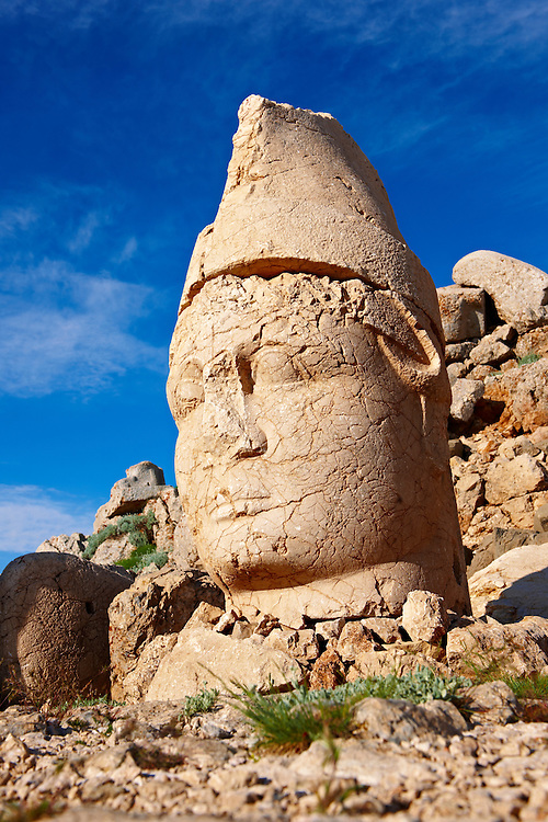 Pictures of the statues of around the tomb of Commagene King Antochus 1 on the top of Mount Nemrut, Turkey. Stock photos & Photo art prints. In 62 BC, King Antiochus I Theos of Commagene built on the mountain top a tomb-sanctuary flanked by huge statues (8–9 m/26–30 ft high) of himself, two lions, two eagles and various Greek, Armenian, and Iranian gods. The photos show the broken statues on the  2,134m (7,001ft)  mountain. 3