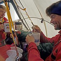 BAFFIN ISLAND, Nunavut, Canada. Jared Ogden & Alex Lowe enjoy a hot drink in portaledge tent high on Great Sail Peak.
