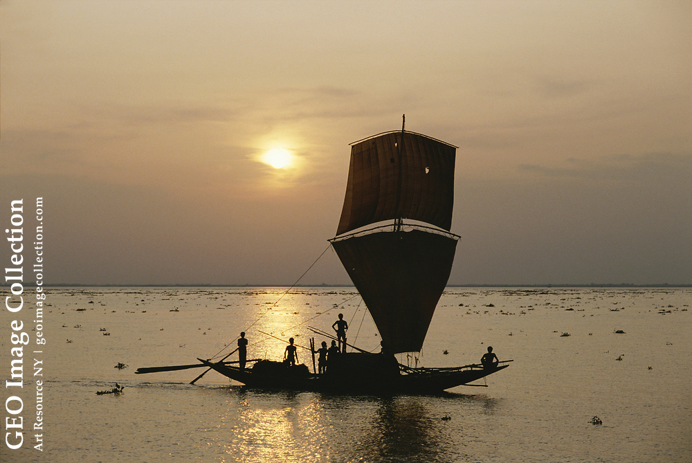 A fishing boat on the Meghna River at sunset.