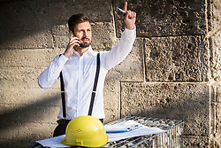 Male architect talking on mobile phone with blueprint at construction site, Munich, Bavaria, Germany