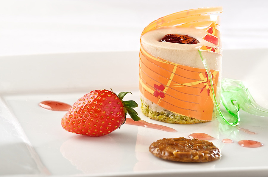 Citrus mousse topped with chardonnay poached, mixed fruit, wrapped with rolled meringue and cocoa nib macaroon bottom, served with raspberry coulis.