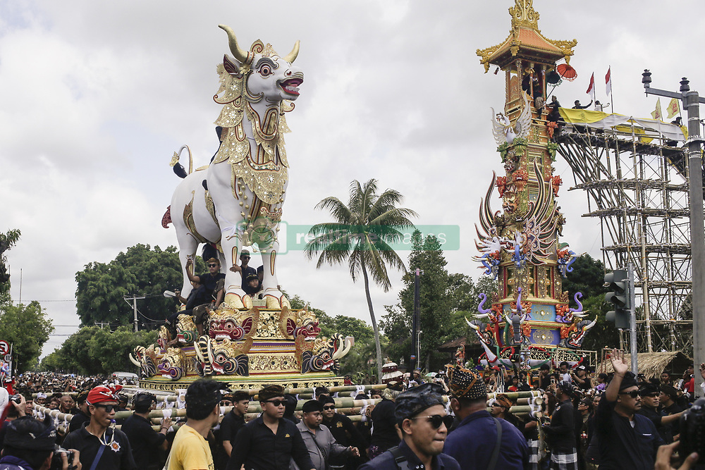 December 18, 2018 - Bali, Bali, Indonesia - Balinese carries a white-bull sarcophagus and 24-meters tall tower or Bade that transport the royal corpse to cemetery during royal cremation ceremony known as Pelebon in Gianyar, Bali, Indonesia on December 18 2018. The ritual is to honor the deceased, Ida I Gusti Ngurah Djelantik XXIV, an elder of Puri Ageng Blahbatuh royal family. (Credit Image: © Johanes Christo/NurPhoto via ZUMA Press)