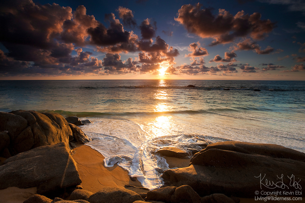 The sun begins to set over the Pacific Ocean as waves crash up against the rocks on the beach near Sayulita, Mexico.