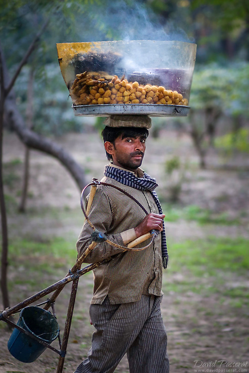 Donut street seller carrying his wares and craft stove. His donuts are still steaming from cooking.