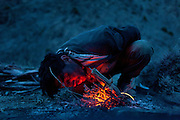 A Kyrgyz man starts fire to cook salty milk tea. Trekking up and along the Wakhan river, the only way to reach the high altitude Little Pamir plateau, home of the Afghan Kyrgyz community.