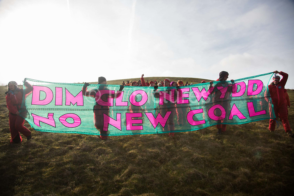 Under the banner, in Welsh and English, No More Coal the activists head towards the mine. Hundreds of environmental activists stopping the open cast coal mine Ffos-y-Fran near Merthyr Tydfil, Wales from operating May 3rd 2016. Under the banner, in Welsh and English, No More Coal the activists head towards the mine.The activists from Reclaim the Power wants the mine shut down and a moratorium on all future open coal mining in Wales. The group Reclaim the Power had set up camp near by and had over three days prepared the action and up to 300 activists all dressed in red went into the mine in the early morning. The activist were plit in three groups and carried various props signifying the red line in the sand, initially drawn in Paris at the COP21. The mine is one of the largest open cast coal mines in the UK and is run by Miller Argent who have to date extracted 5million tons of coal. The activists entered the mine unchallenged by any security or police and the protest went on peacefully till mid afternoon with no arrests made.  Open coal mining is hugely damaging to the local environment and  contributing to global climate change.