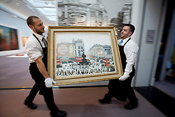 """© Licensed to London News Pictures. 21/03/2014. London, UK. Sotheby's auction house staff move """"Piccadilly Circus London"""" (1960) (est. GB£4,000,000-6,000,000) by British artist LS Lowry during the press view for a new sale of the artist's work in London today (21/03/2014). The auction, entitled """"Lowry: The AJ Thompson Collection"""", features works by Lowry assembled over a 30 year period by collector A.J. Thompson. Photo credit: Matt Cetti-Roberts/LNP"""