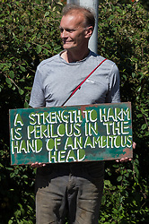 Harefield, UK. 31st July, 2020. An environmental activist opposed to the HS2 high-speed rail link takes part in the restating of a historical 1602 visit by Queen Elizabeth I to Dews Farm. The activists tried to retrace the steps of Queen Elizabeth I from St Mary's church to Dews Farm in order to pay their respects to Anne and Ron Ryall, 73 and 72, on the day of their eviction from Dews Farm by HS2 after having spent nine years and their life savings renovating their £1m dream home, but found their path blocked by HS2 fences and security guards.