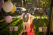 Denzel Tolliver gets some assistance with his jacket while posing for pictures on the red carpet in from of his date Kietta Saunders' home before heading to prom Friday, May 9, 2014 in Elmwood Park. (Brian Cassella/Chicago Tribune) B583716571Z.1 <br /> ....OUTSIDE TRIBUNE CO.- NO MAGS,  NO SALES, NO INTERNET, NO TV, CHICAGO OUT, NO DIGITAL MANIPULATION...