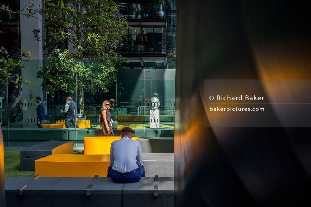A passing lady notices another office worker outside outside the Leadenhall Building during the 2018 heatwave in the City of London, the capital's financial district, on 24th July 2018, in London, England.