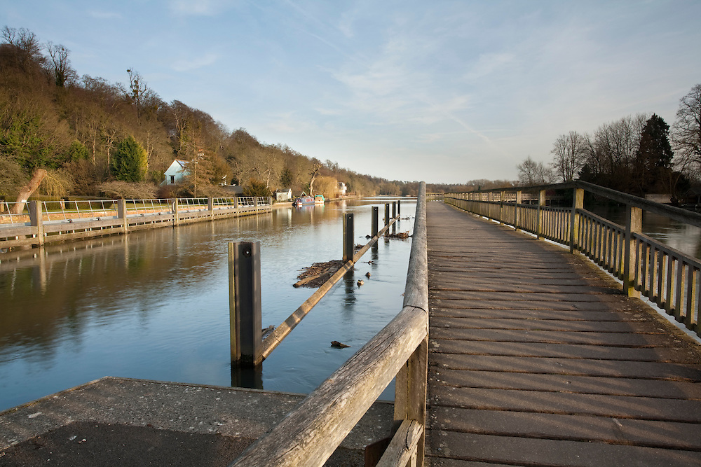 Looking along the wooden footbridge over the River Thames from Marsh Lock near Henley on Thames, Uk