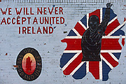 With the words 'We will never accept a united Ireland' and another quote 'For God and Ulster' we see a detail of a political painting in a street off the Shankhill Road in Belfast, Northern Ireland. This Loyalist mural may have been drawn by a paramilitary artist, whose handiwork is the crest of the protestant Ulster Defence Association (UDA) and the Ulster Volunteer Force (UVF) the organisations behind many a sectarian action against neighbouring catholic supporters of the Irish republican Army (IRA). In loyalist areas, the red, white and blue of the British Union Jack is painted on kerbs, houses and railings to signify peoples' allegiance to the crown, having historically followed the 17th century activities of King William of Orange against Catholics.