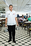A waiter holds a pot of hot coffee and one of hot milk as he waits for a customer to tap their glass at the iconic Gran Café de La Parroquia along the Malecon in Veracruz City, Mexico. The cafe is known for their long pours of hot milky coffee known as a lechero which they have served since 1808 and in their current form has operated continuously since 1926.