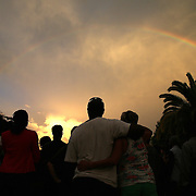 """A rainbow is seen over Lake Eola park during the """"National Moment of Silence"""" event at the Lake Eola bandshell in downtown Orlando, Florida on Thursday, August 14, 2014. In light of the recent killing of eighteen year old Mike Brown in Ferguson, Missouri, citizens across America are gathering in solidarity to hold vigils and observe a moment of silence to honor victims of suspected police brutality. (AP Photo/Alex Menendez)"""