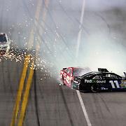 NASCAR Sprint Cup drivers Denny Hamlin (11) and Juan Pablo Montoya (42) crash on the front stretch during the NASCAR Coke Zero 400 Sprint series auto race at the Daytona International Speedway on Saturday, July 6, 2013 in Daytona Beach, Florida.  (AP Photo/Alex Menendez)