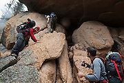 Marco Binotti (l-r), David Coffey, and Obadiah Reid take shelter from a storm inside a small cave in the Lost Creek Wilderness, Colorado.
