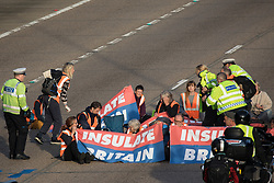Ockham, UK. 21st September, 2021. Surrey Police officers detain an Insulate Britain climate activist on the clockwise carriageway of the M25 between Junctions 9 and 10. Activists briefly halted traffic on both carriageways as part of a campaign intended to push the UK government to make significant legislative change to start lowering emissions before being removed and arrested by Surrey Police.