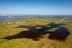 Aerial view from drone of village of Geirinis and ruin of Dun Mor broch on island in South Uist, Outer Hebrides, Scotland, UK