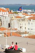Two ladies enjoying the sun at Portas do Sol esplanade in Lisbon.