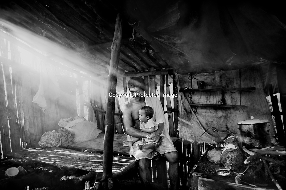 Don Moises with his grandchild in the small kitchen. the money are very small in the family and the food are most days the same. Moises's daughter is home from one of the islands where she is working, just to help her family. Story about divers in Honduras.