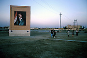 Boys play football in the late afternoon by a poster of Saddam Hussein. Basra, Iraq