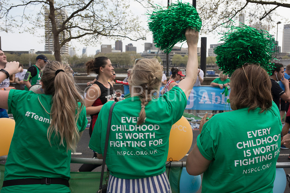 Charity supporters from NSPCC encourage participants taking part in the London Marathon on 22nd April 2018 in London, England, United Kingdom. The London Marathon, presently known through sponsorship as the Virgin Money London Marathon, is a long-distance running event. The event was first run in 1981 and has been held in the spring of every year since. The race is mainly known for ebing a public race where ordinary people can challenge themsleves while raising great amounts of money for various charities.