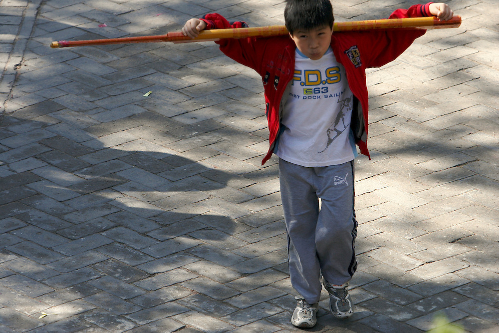 A boy carries a large stick of incense towards the last center hall at  Baiyuguan.  Baiyuguan,called White Cloud Temple in English, is over 1,200 years old and stands the south west of Beijing, China.  White Cloud Temple is the largest Daoist structure in Beijing and home of the Dragon Gate sect of Daoism.